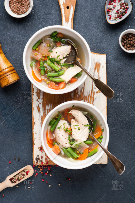 Two served bowls of chicken soup from above. Broth with chicken, mung and green beans