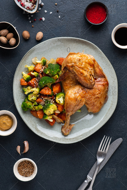 Roasted chicken served on plate with broccoli and sweet potato over dark background