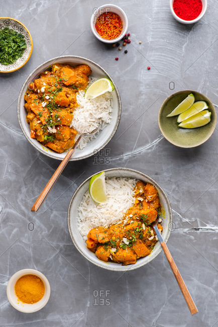 Indian food Curry butter chicken in bowls with basmati rice on gray background