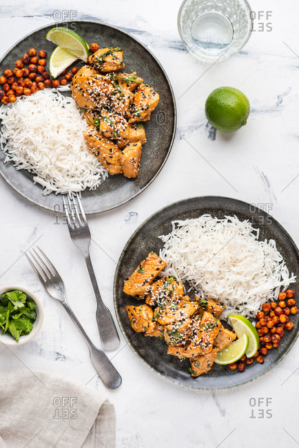 Overhead view of fried chicken with basmati rice and smoky roasted chickpeas served on ceramic plates