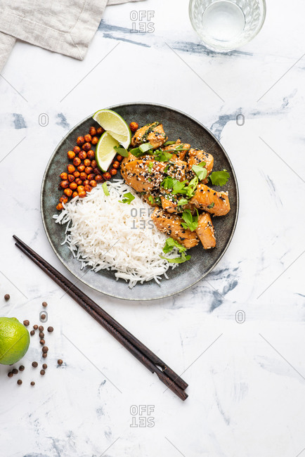Overhead view of fried chicken with basmati rice and smoky roasted chickpeas served on ceramic plate