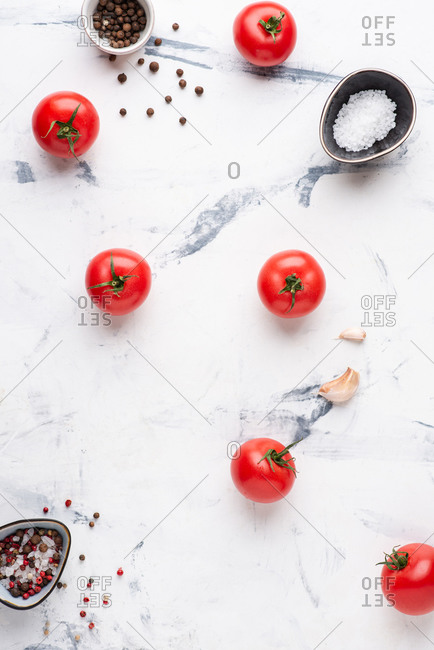 Set of fresh tomatoes and spices over white background