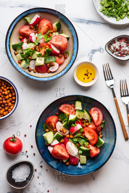 Fresh vegetable salad with tomatoes, cucumbers and radishes served in blue ceramic bowls over white background