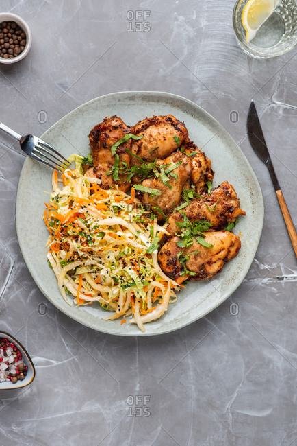 Roasted chicken bites with cabbage salad on a plate over gray background