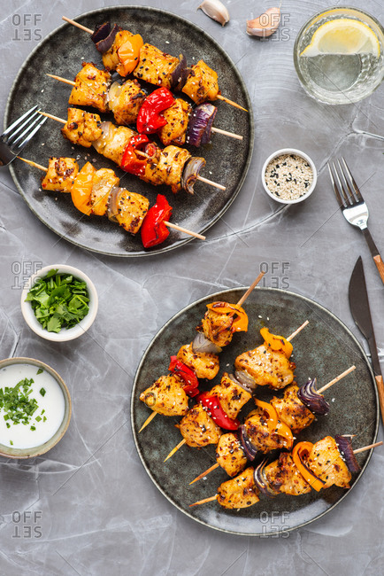 Skewers of chicken breast with grilled bell pepper and red onion served on dark ceramic plate