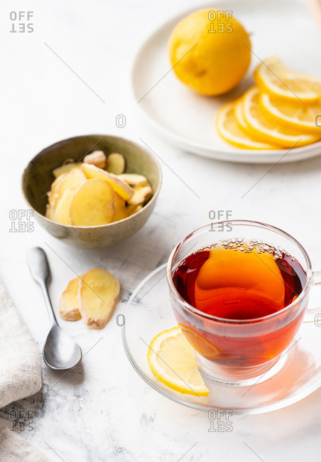 Cup of tea with lemon and ginger and honey in a glass jar on the background
