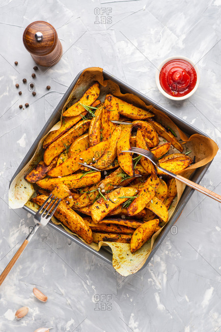 Baked potato wedges with sea salt, ketchup and rosemary
