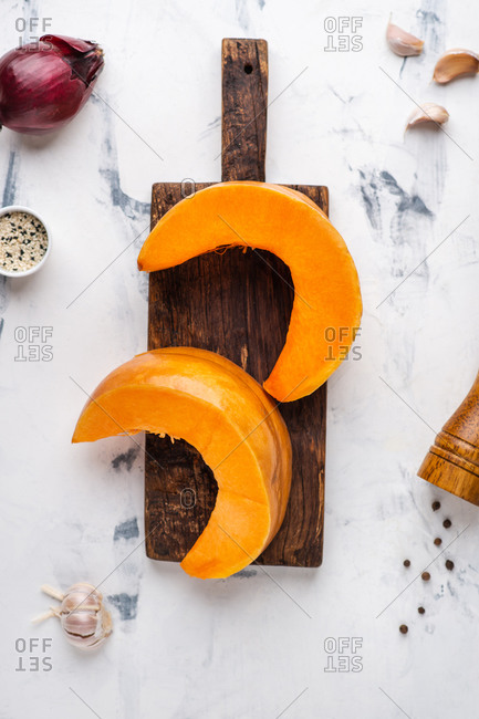 Overhead view of sliced pumpkin on dark wooden chopping board over white background