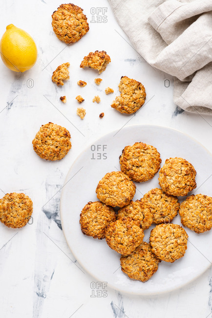 Overhead view of freshly baked oatmeal cookies served on plate over white background