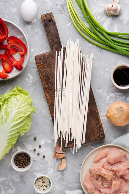 Ingredients for cooking Asian food. Fresh chicken meat, vegetables and spices for cooking Asian udon noodle dish on gray background