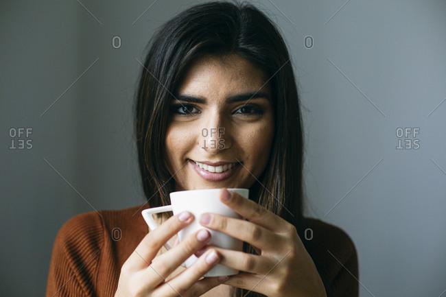 Portrait of smiling businesswoman enjoying coffee in break at office