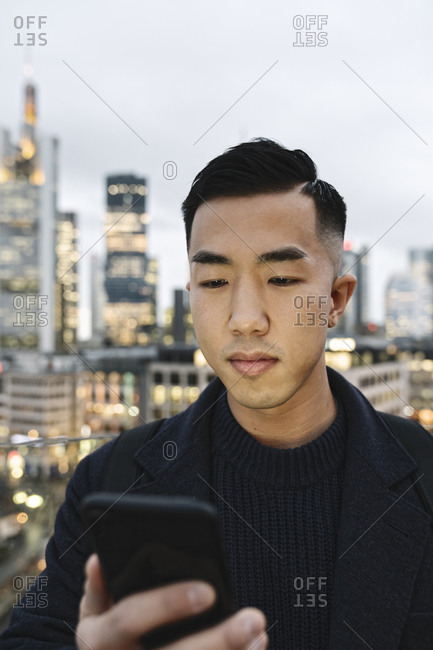 Portrait of man using smartphone in the city at dusk