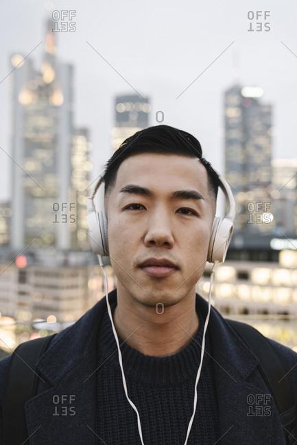 Portrait of man with headphones in front of urban skyline- Frankfurt- Germany