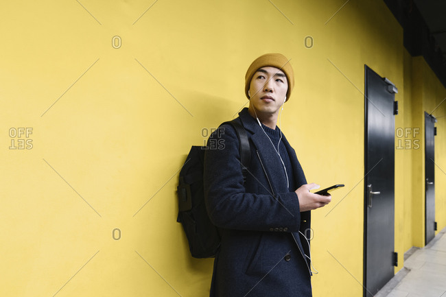 Stylish man with yellow hat and earphones using smartphone