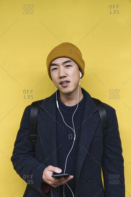 Portrait of stylish man with yellow hat and earphones using smartphone