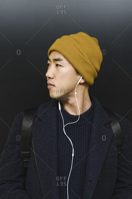 Portrait of stylish man with yellow hat and earphones