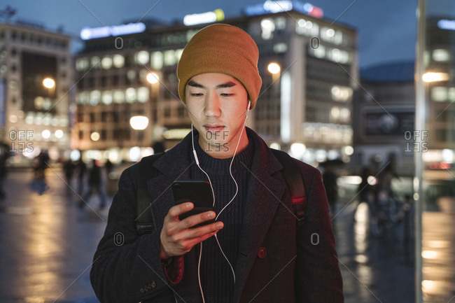 Man with earphones using smartphone in the city at night