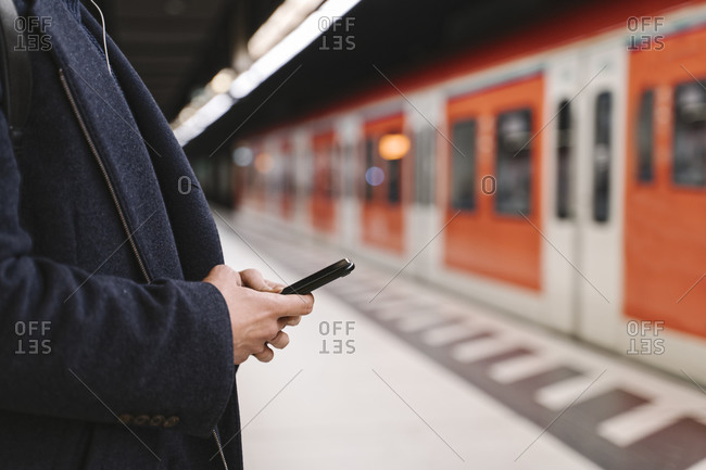 Close-up of man using smartphone in metro station