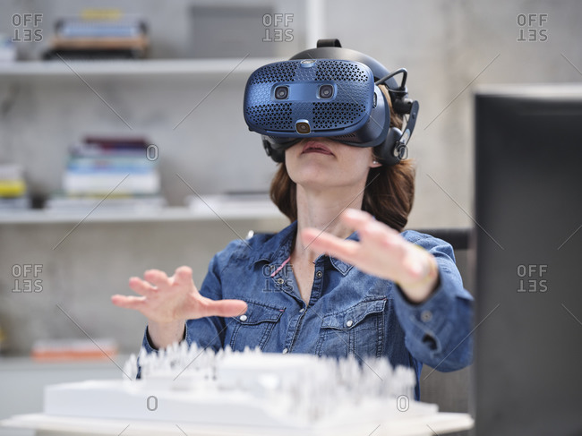 Woman wearing VR glasses and headset in modern office