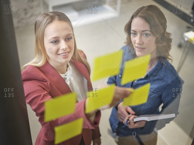 Two businesswomen working on sticky notes at glass pane in office