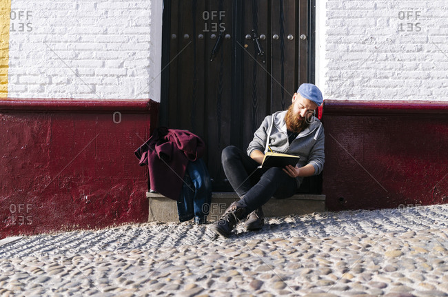 Man sitting on front stoop in the city drawing a sketch- Granada- Spain