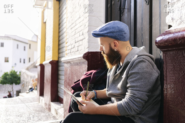Man sitting at entrance door in the city drawing a sketch- Granada- Spain