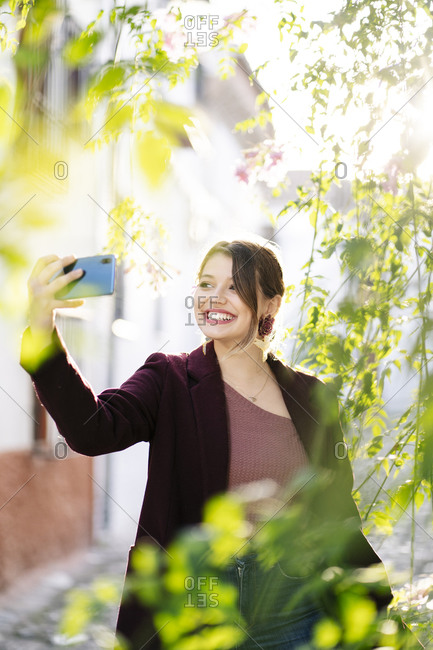 Smiling woman taking a selfie in a scenic alley in the city