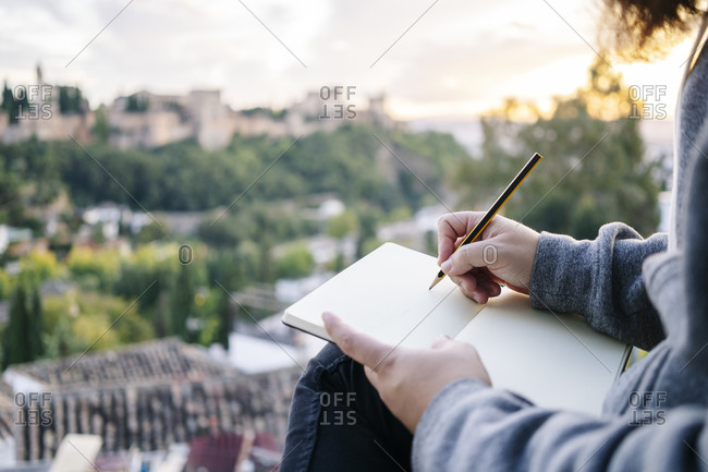 Close-up of man at observation point drawing a sketch of the Alhambra- Granada- Spain