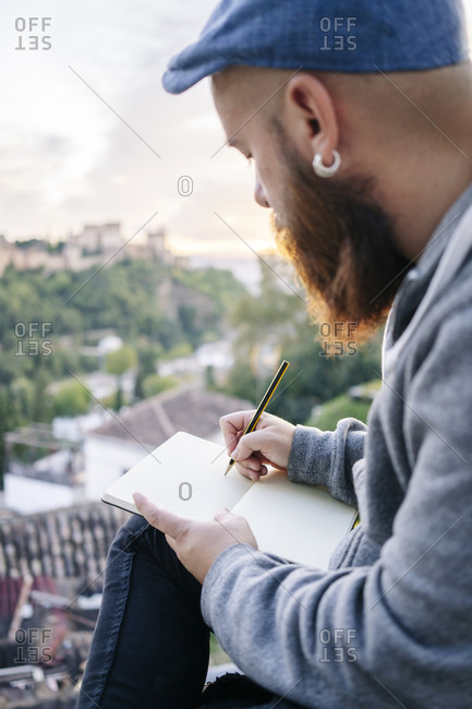 Man at observation point drawing a sketch of the Alhambra- Granada- Spain