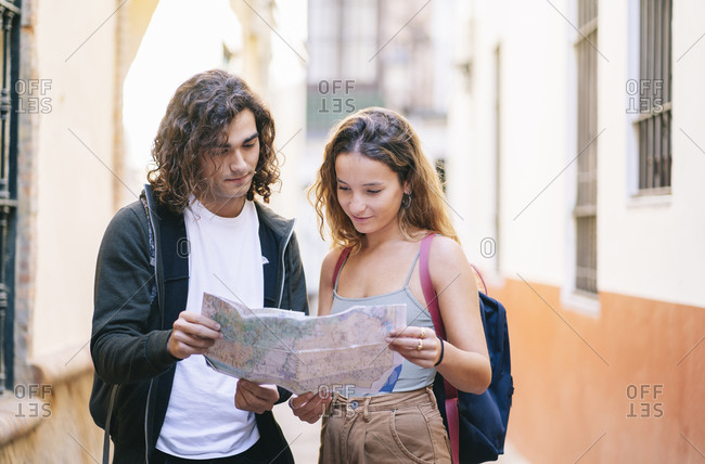 Boyfriend and girlfriend reading map while standing on narrow street at Santa Cruz- Seville- Spain