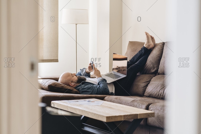 Businessman with laptop listening music through smart phone while lying on sofa at home