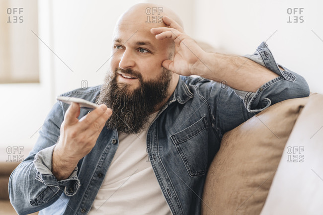 Businessman with shaved head talking over speaker on smart phone while sitting on sofa at home