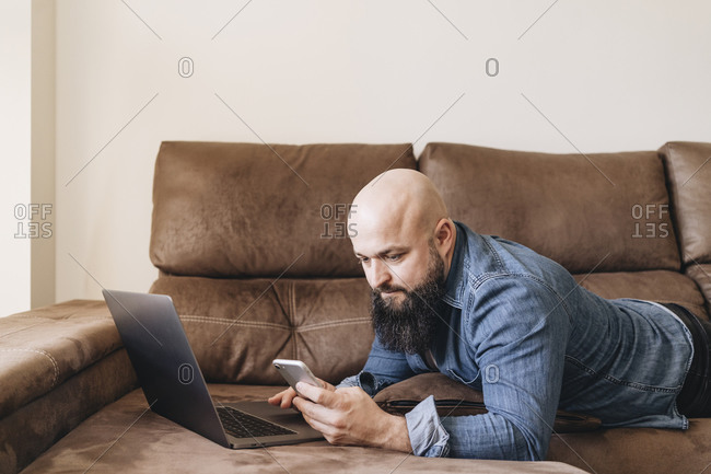 Businessman with laptop using mobile phone while lying on sofa at home
