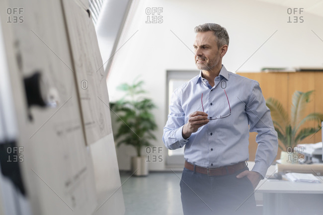 Confident businessman looking at plan in office