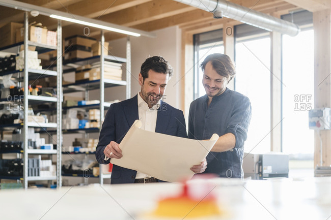 Smiling businessman and employee discussing plan in factory