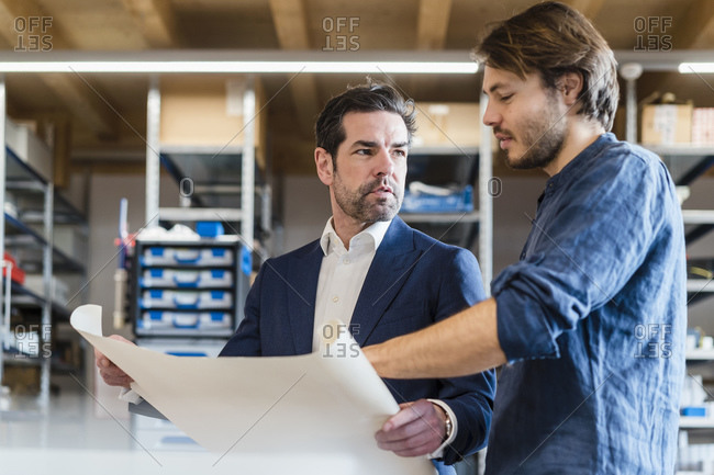 Businessman and employee discussing plan in factory