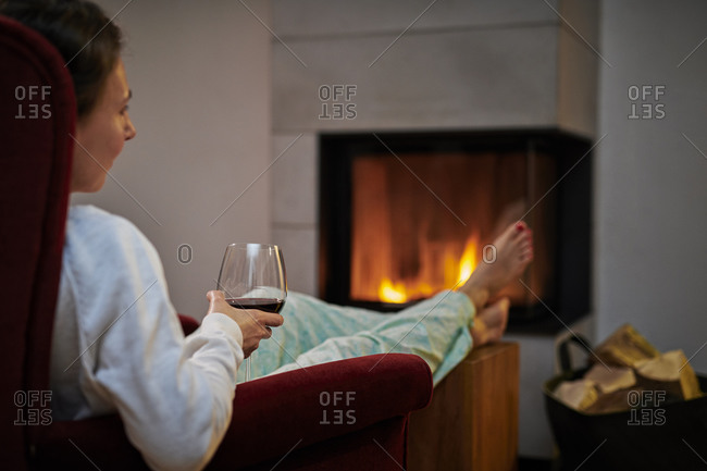 Woman sitting on armchair with glass of red wine relaxing in front of fireplace