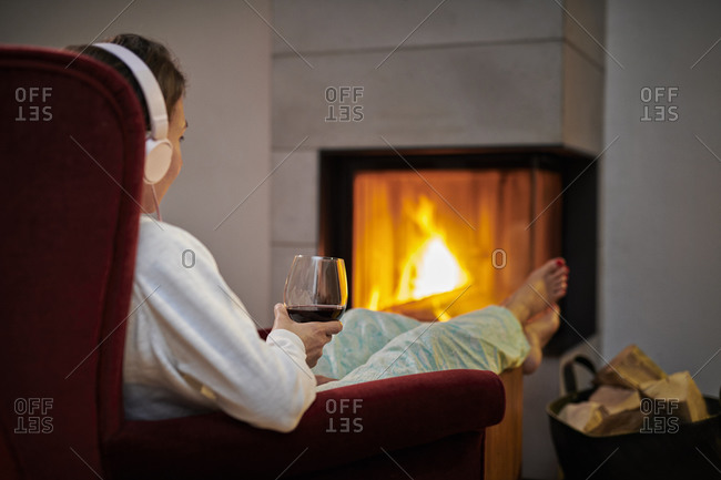 Woman sitting on armchair with glass of red wine listening music with headphones in front of fireplace