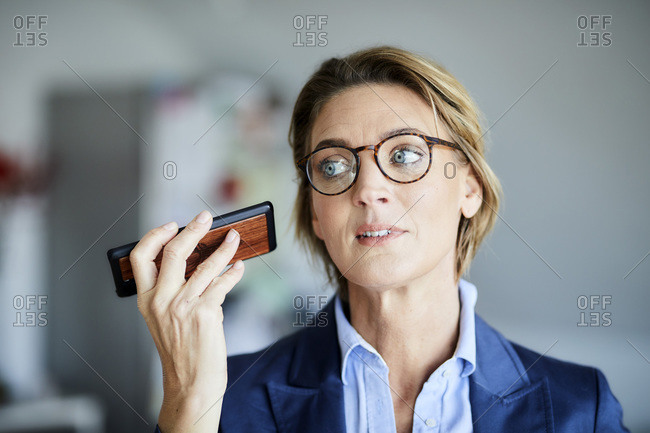 Businesswoman listening to voice mail on her phone