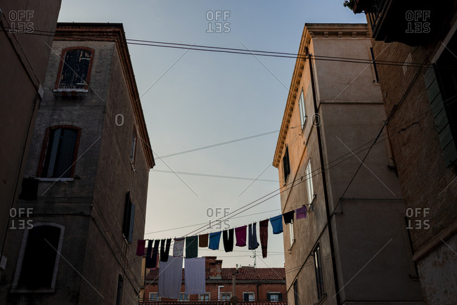 Italy- Venice- Laundry drying on clothesline hanging between two houses