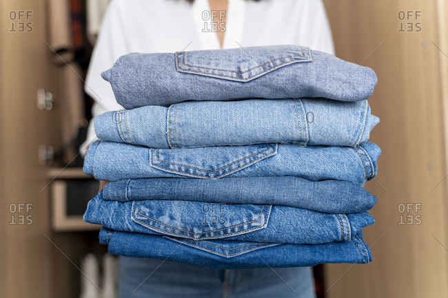 Woman holding stack of blue jeans
