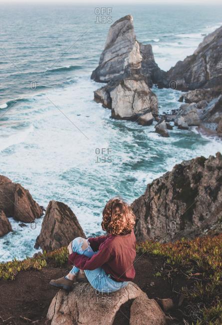 Young woman sitting on viewpoint at Praia da Ursa- Lisboa- Portugal