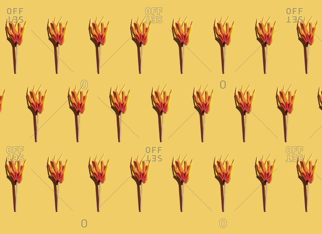 Pattern of matches with cardboard flame against yellow background