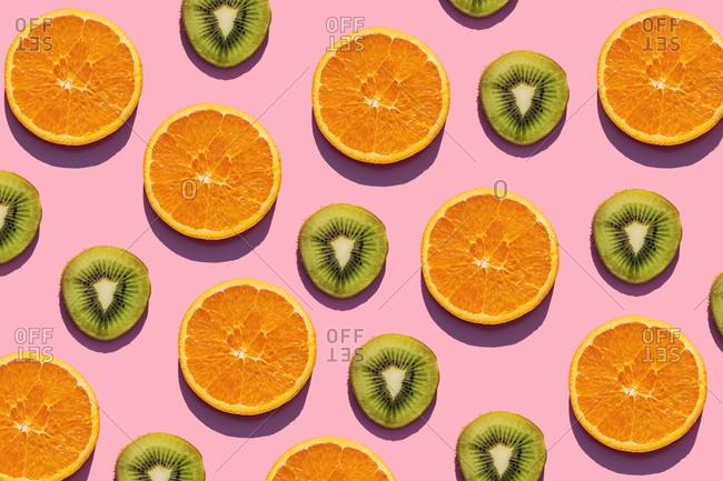 Pattern of orange and kiwi fruit slices against pink background