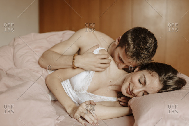 Intimate young couple lying in bed