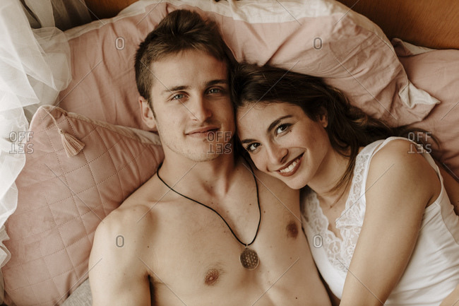 Portrait of happy young couple lying in bed