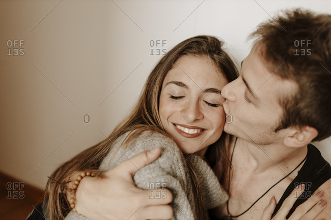 Happy young couple hugging and kissing at home