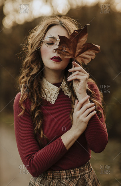 Portrait of fashionable woman with autumn leaf