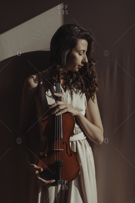 Woman holding violin with closed eyes