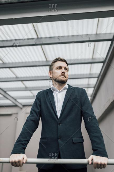 Portrait of brunette businessman leaning on railing